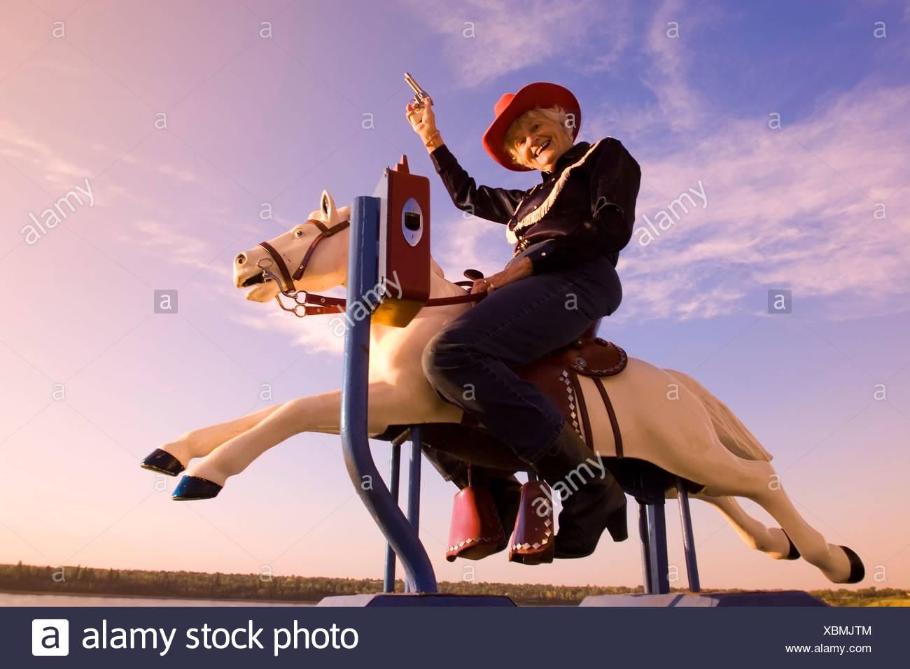 Ältere Frau mechanische Reitpferd Cowboy Kostüm, Kanada. Stockbild