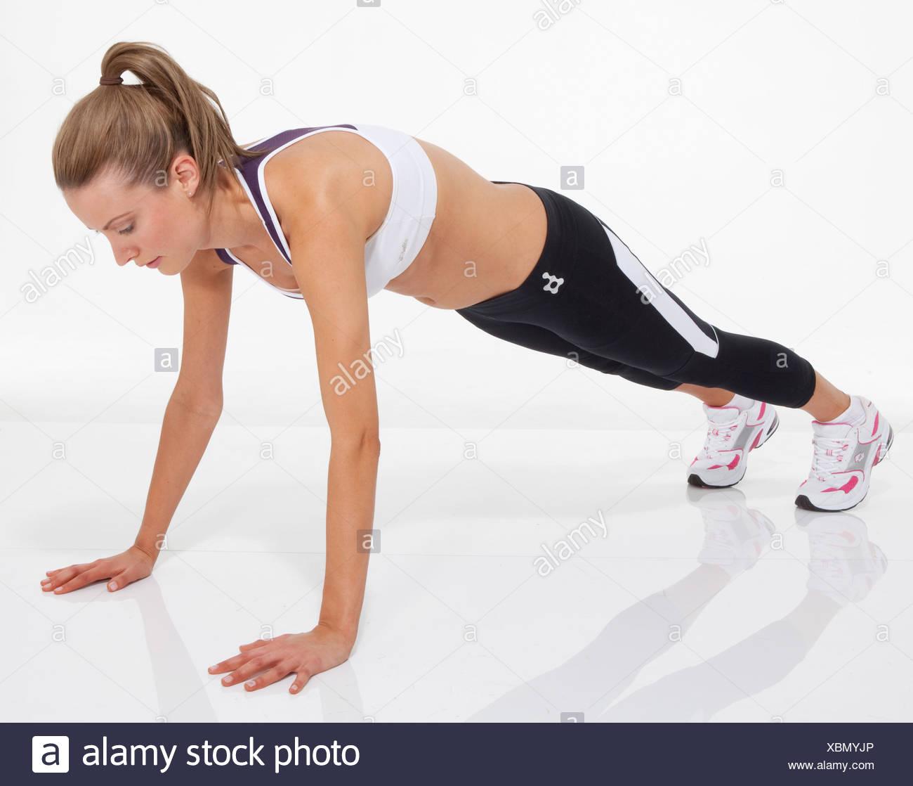 Oberkörper trainieren weibliche blondes Haar gebunden zu Pferdeschwanz tragen eine kurze Weste, schwarze Leggings und Trainer, Durchführung einer Stockbild
