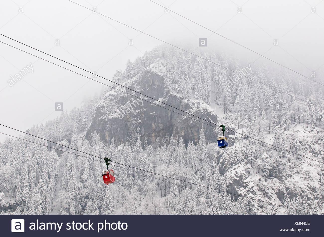 Zwei Autos der Kampenwandbahn Seilbahn vor einem schneebedeckten Berg, Aschau, Chiemgau, Bayern, Deutschland, Europa Stockbild
