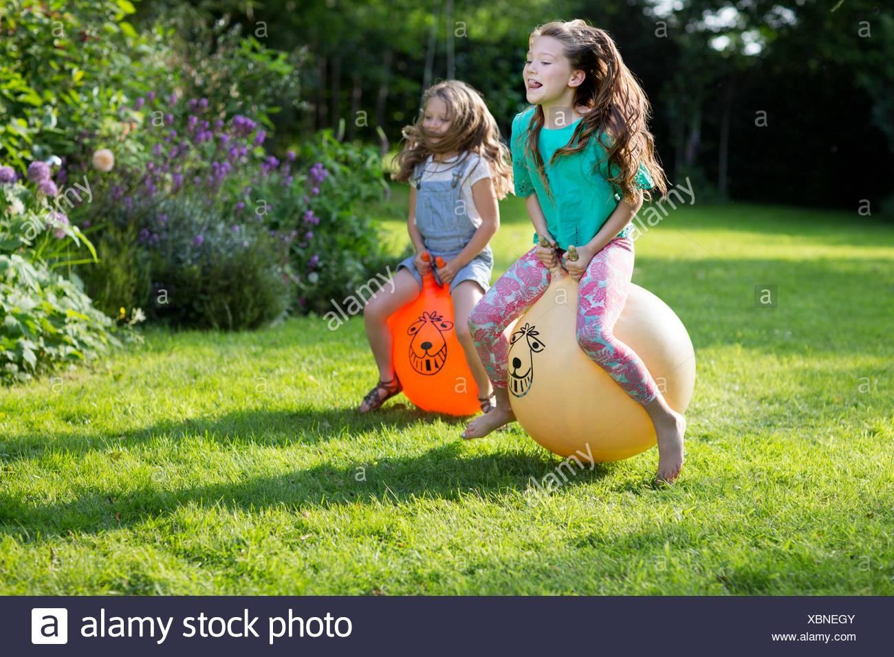 EIGENTUM FREIGEGEBEN. -MODELL VERÖFFENTLICHT. Zwei Schwestern Prellen auf bouncy Trichter im Garten. Stockbild