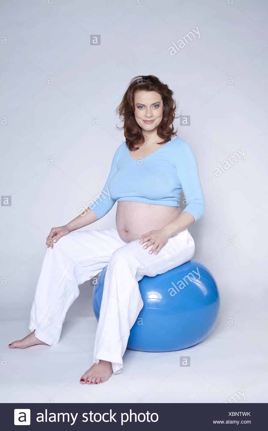 Schwanger, Gymnastik Ball sitzen, Lächeln, genießen Leute, Frau, Studio, Risikoschwangerschaft, schwanger, Brünette, Baby-Bauch, Glück, Mutter, Schwangerschaft, Prejoy, Risiko, Event, hoch schwanger, mütterliche Liebe, Erfahrung, Schwangerschaft, Gefühle, Bauch, Gymnastik ball Stockbild