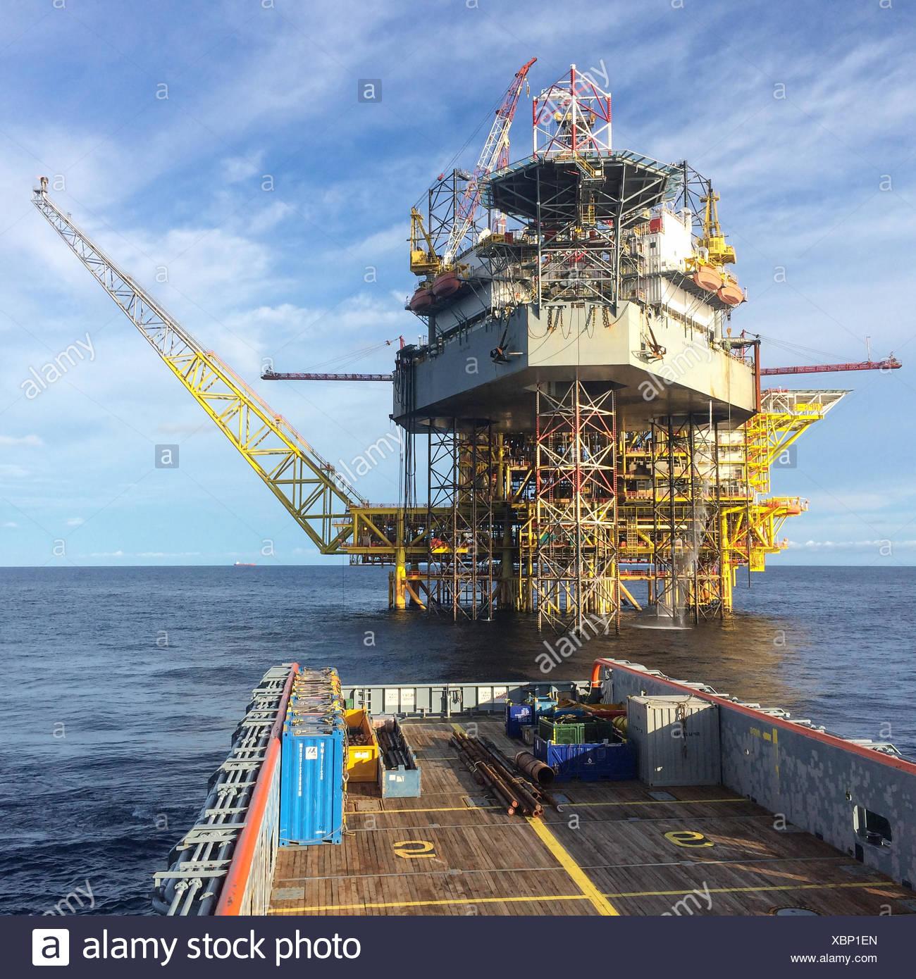 Seeschiff nähert sich einer Ölplattform Stockfoto