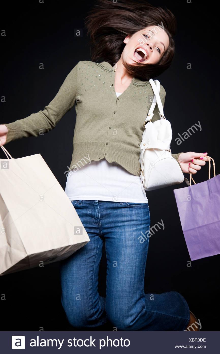 Studio-Porträt der jungen Frau mit Einkaufstüten springen Stockbild