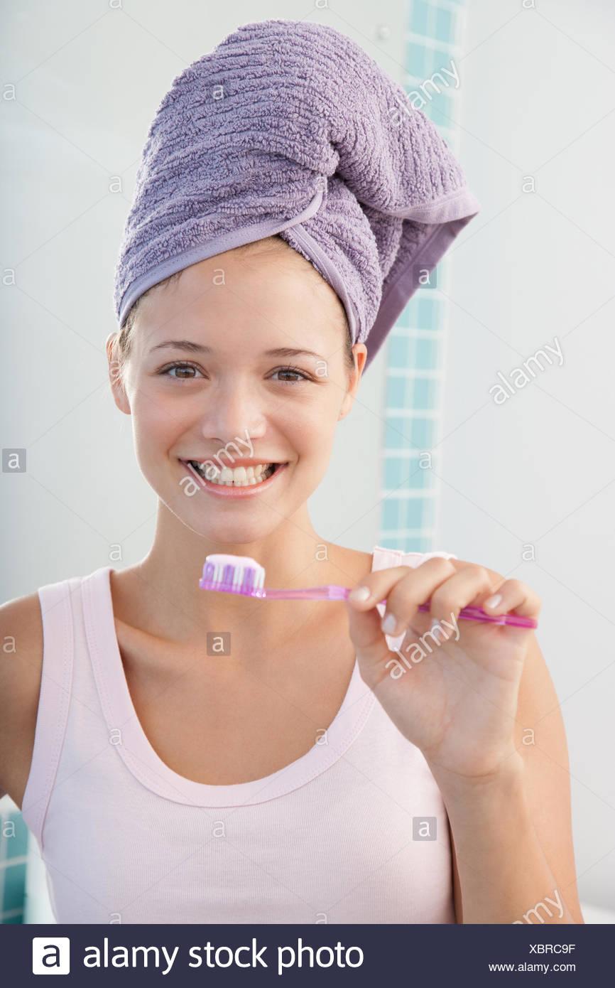 Eine junge Frau, die ihre Zähne putzen Stockbild