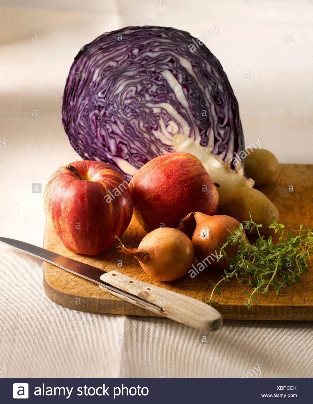 Rotkohl, Äpfel, Kartoffeln, Thymian und Zwiebeln auf Schneidebrett Stockbild