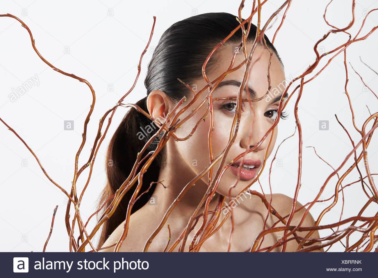 Blick in die Kamera hinter Zweige Frau Stockbild