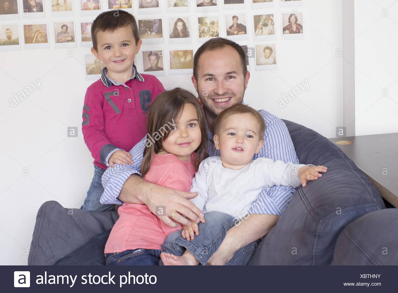 Vater und Kinder sitzen zusammen auf Sofa, Porträt Stockbild