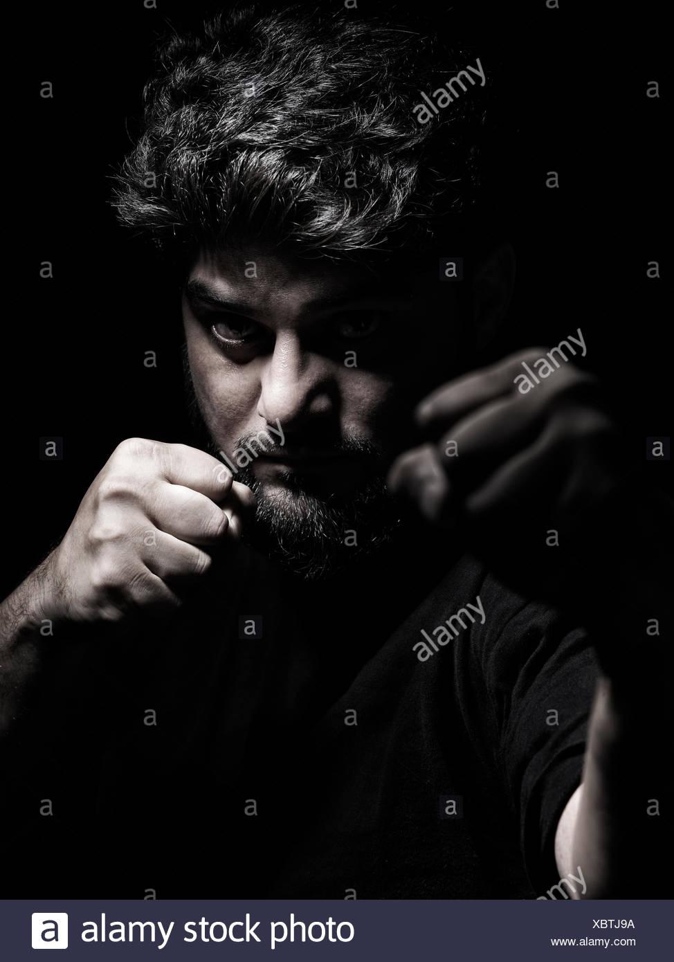 Dramatische Porträt eines Mannes in eine Kampfposition mit Fäusten vor seinem Gesicht Stockbild