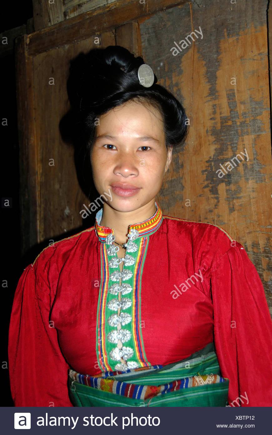 Frau des Stammes Tai Dam mit einem gestapelten Frisur tragen bunten Tracht, Ban Nambone Tai, Phongsali Stockbild