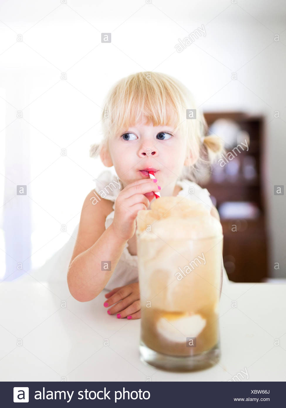 Mädchen (2-3) trinken Milchshake Stockbild