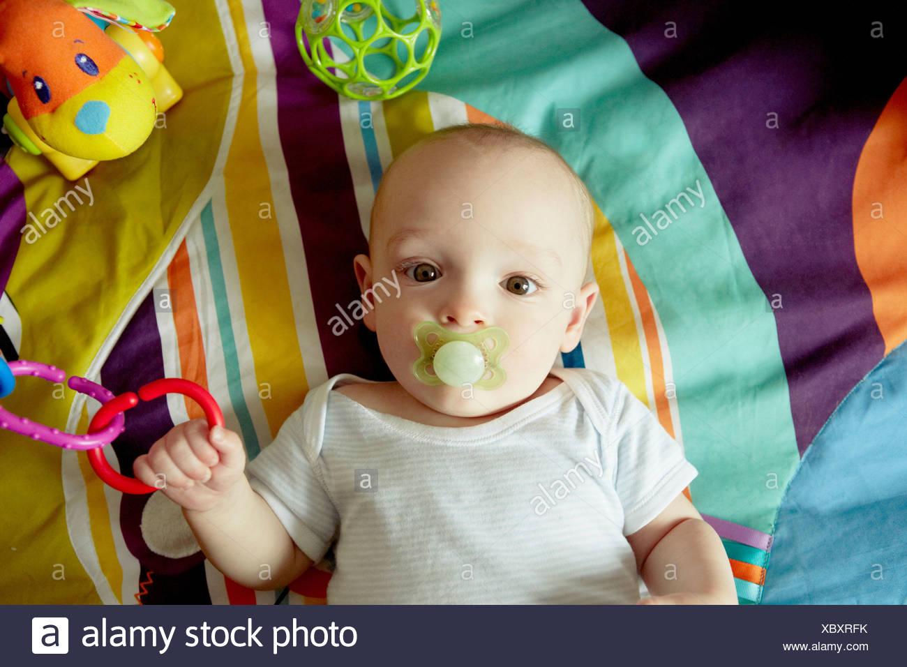 Baby Junge liegend auf Decke Schnuller saugen und spielen mit Spielzeug Stockbild