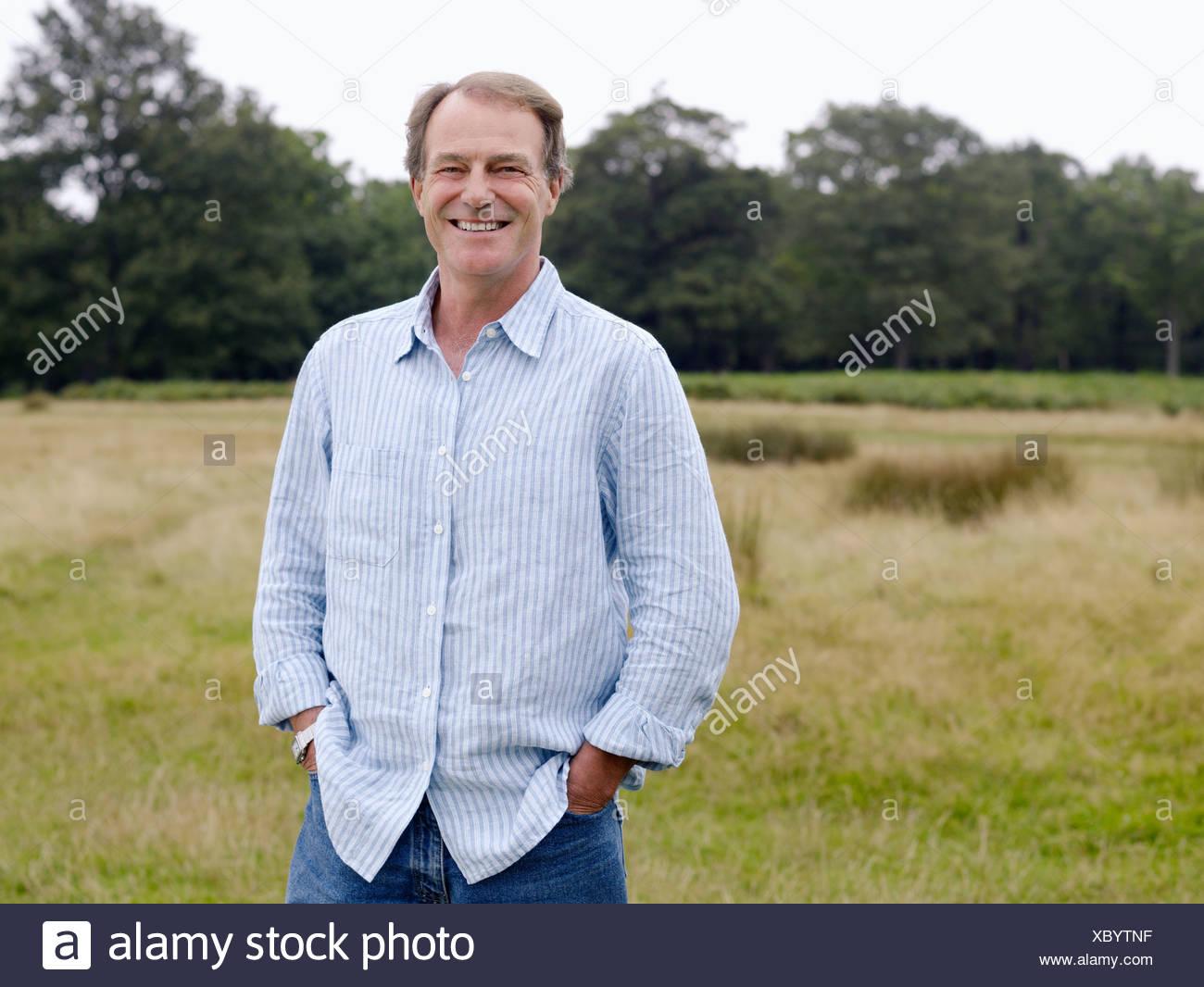 Lächelnde reifer Mann in einem Feld Stockbild