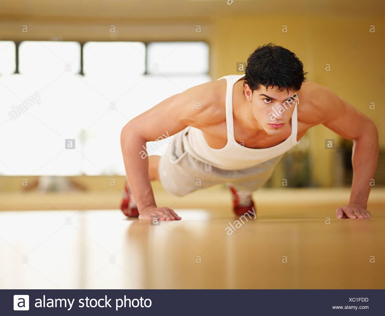 Mann tut Push-ups in einem Fitnessstudio Stockbild