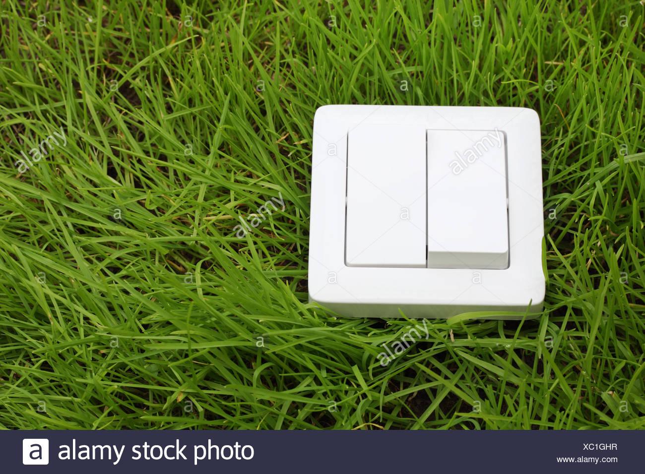 Lichtschalter auf einem grünen Rasen-Hintergrund Stockbild