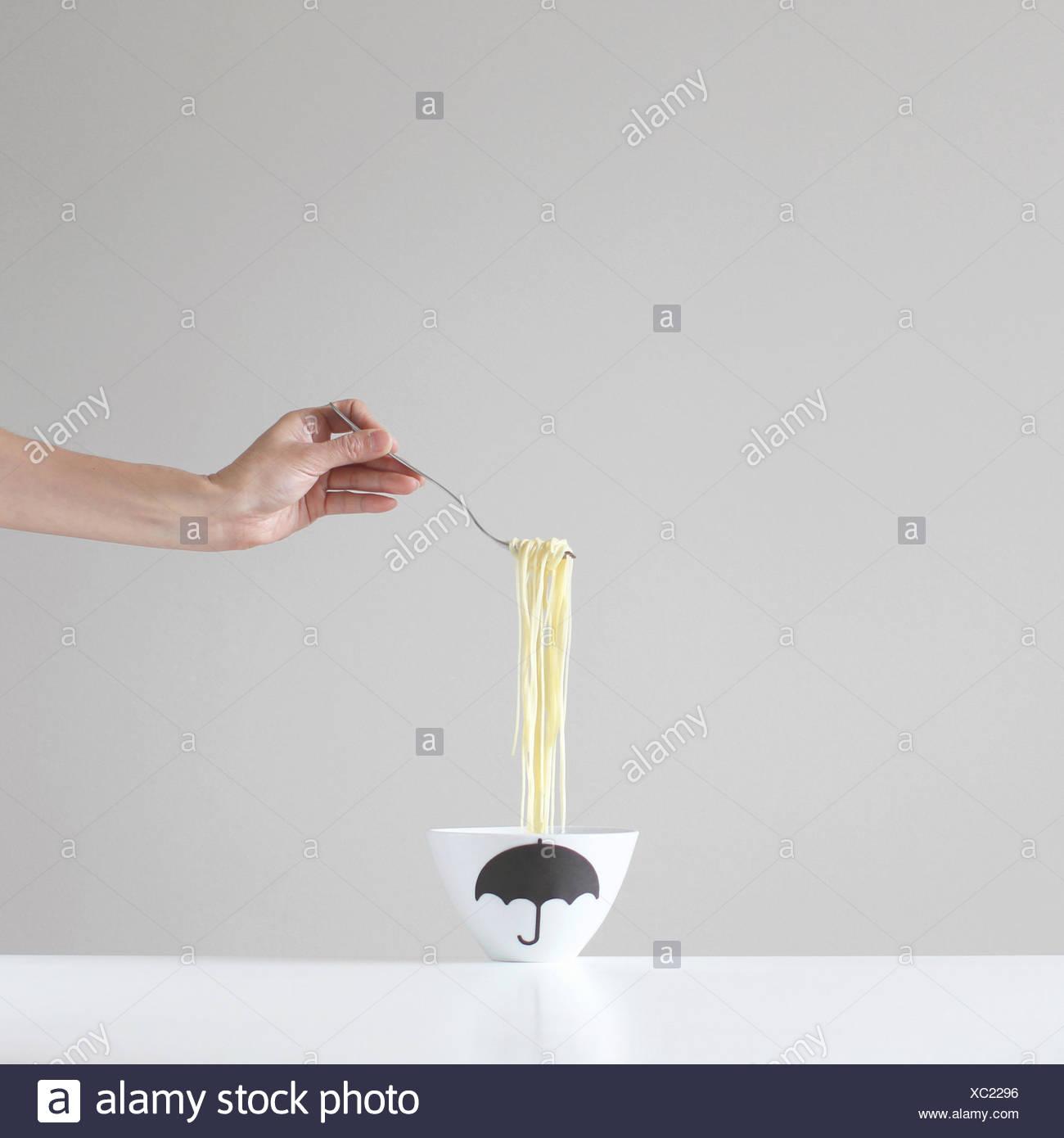 Hand, die eine Gabel Spaghetti über einer Schüssel Stockbild