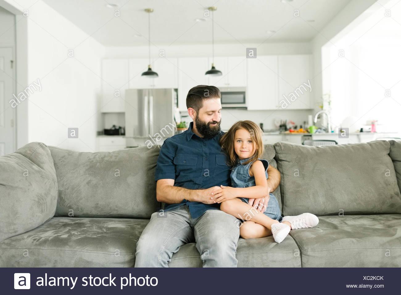 Vater mit Tochter (6-7) sitzen auf dem Sofa im Wohnzimmer. Stockbild