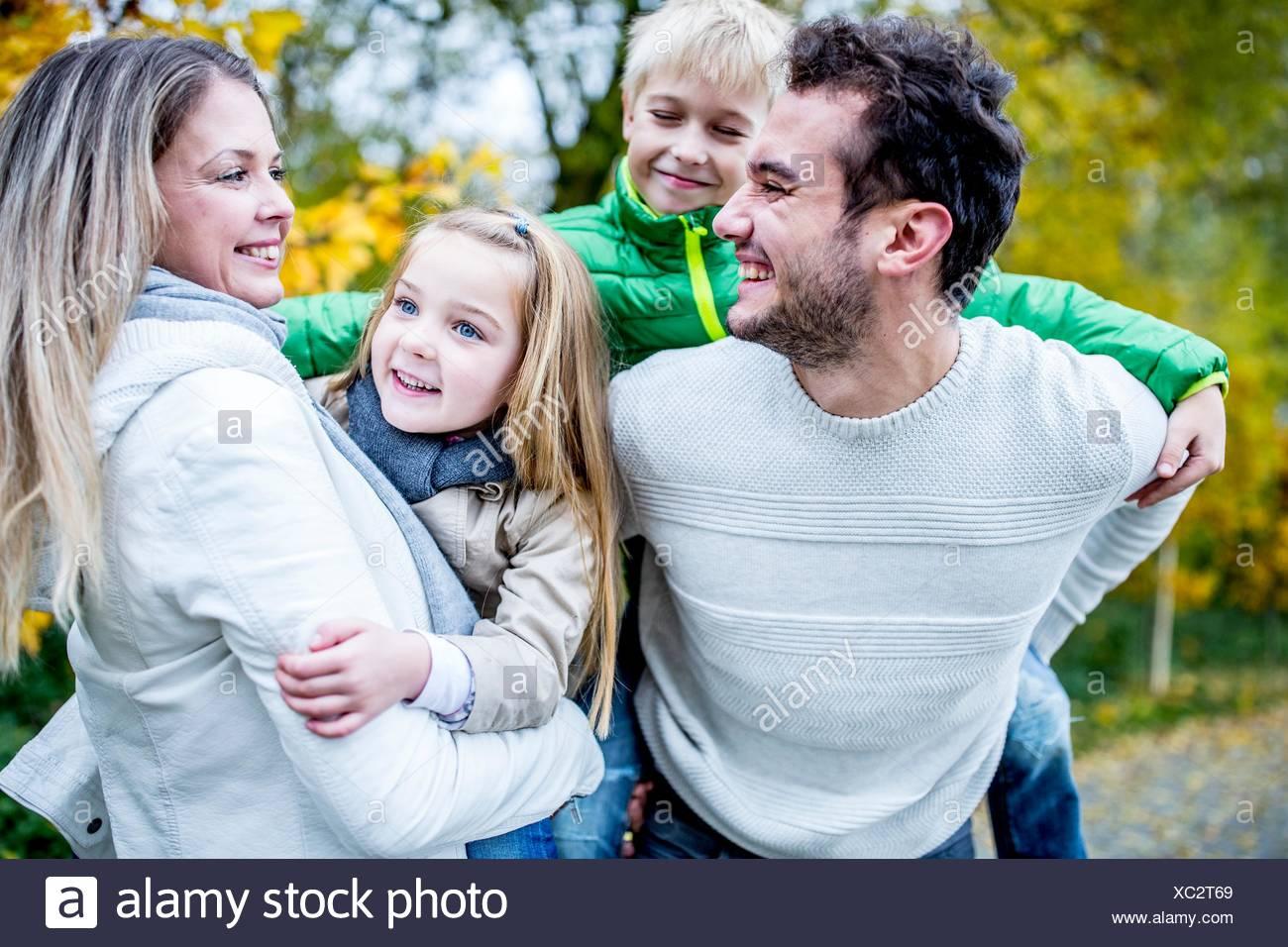 -MODELL VERÖFFENTLICHT. Eltern tragen ihre Kinder im Herbst, lachen. Stockbild