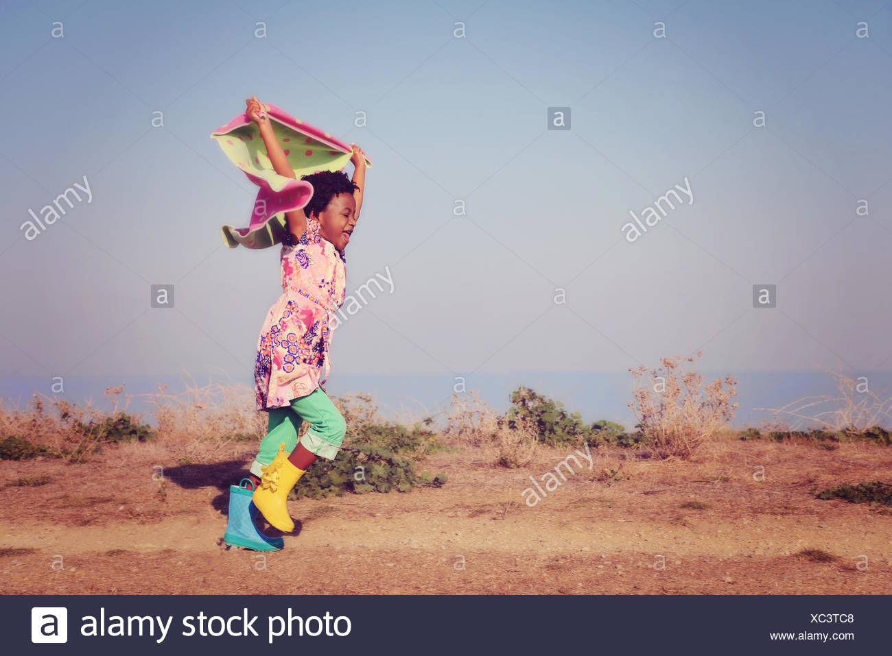 Mädchen laufen halten Schal über dem Kopf Stockbild