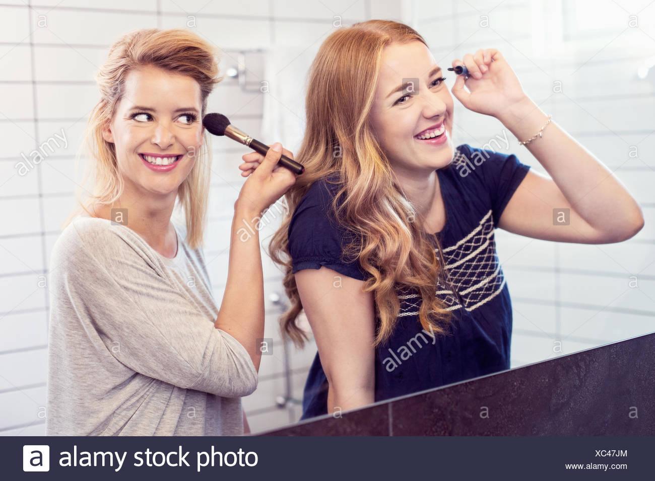Glückliche junge Schwestern Schminken im Spiegel Stockbild