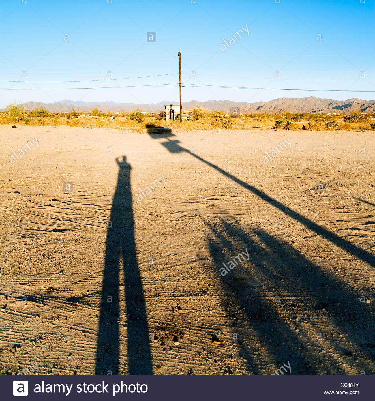 Landschaft mit langen Schatten des Mannes und Wüste im Hintergrund Stockbild