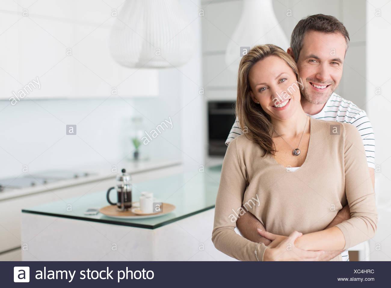 Paar in modernen Küche umarmt Stockbild