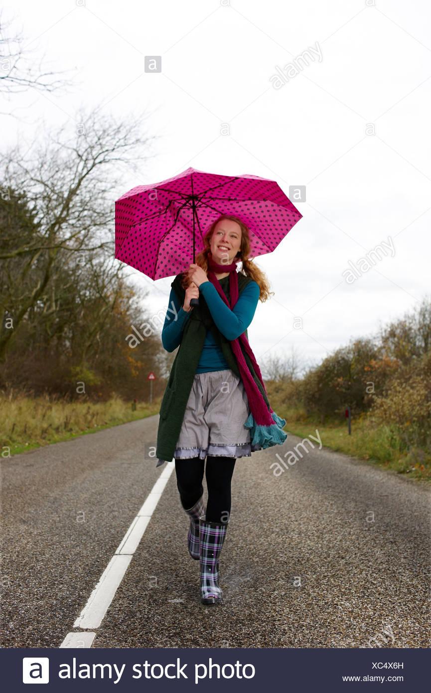 Eine Frau zu Fuß entlang einer Landstraße hält einen rosa Regenschirm Stockbild