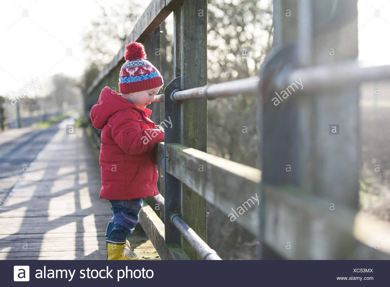 Junge auf einer Brücke nach unten am Fluss Stockbild
