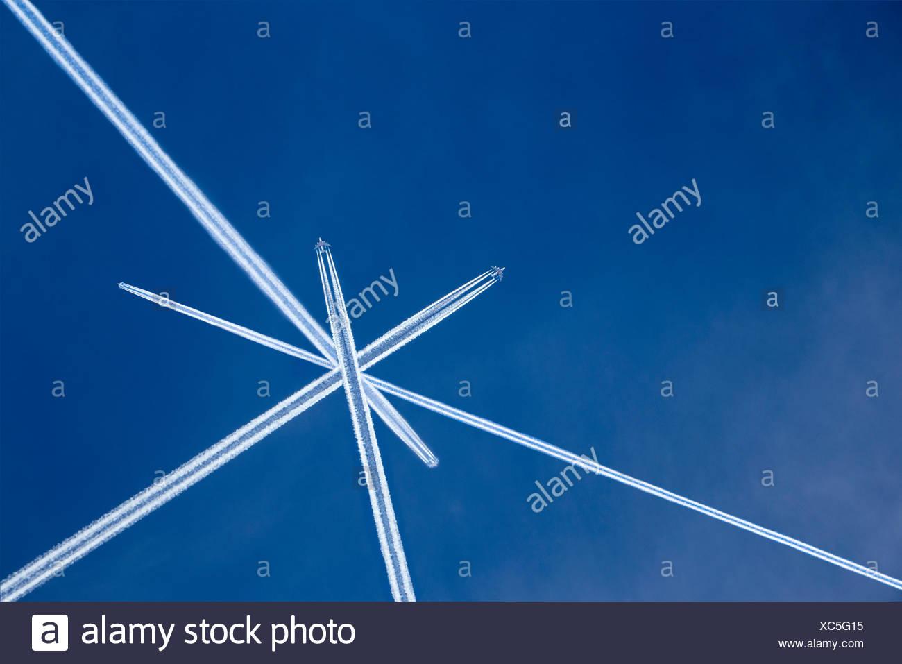Vapor Trails von Flugzeugen im blauen Himmel gekreuzt Stockbild