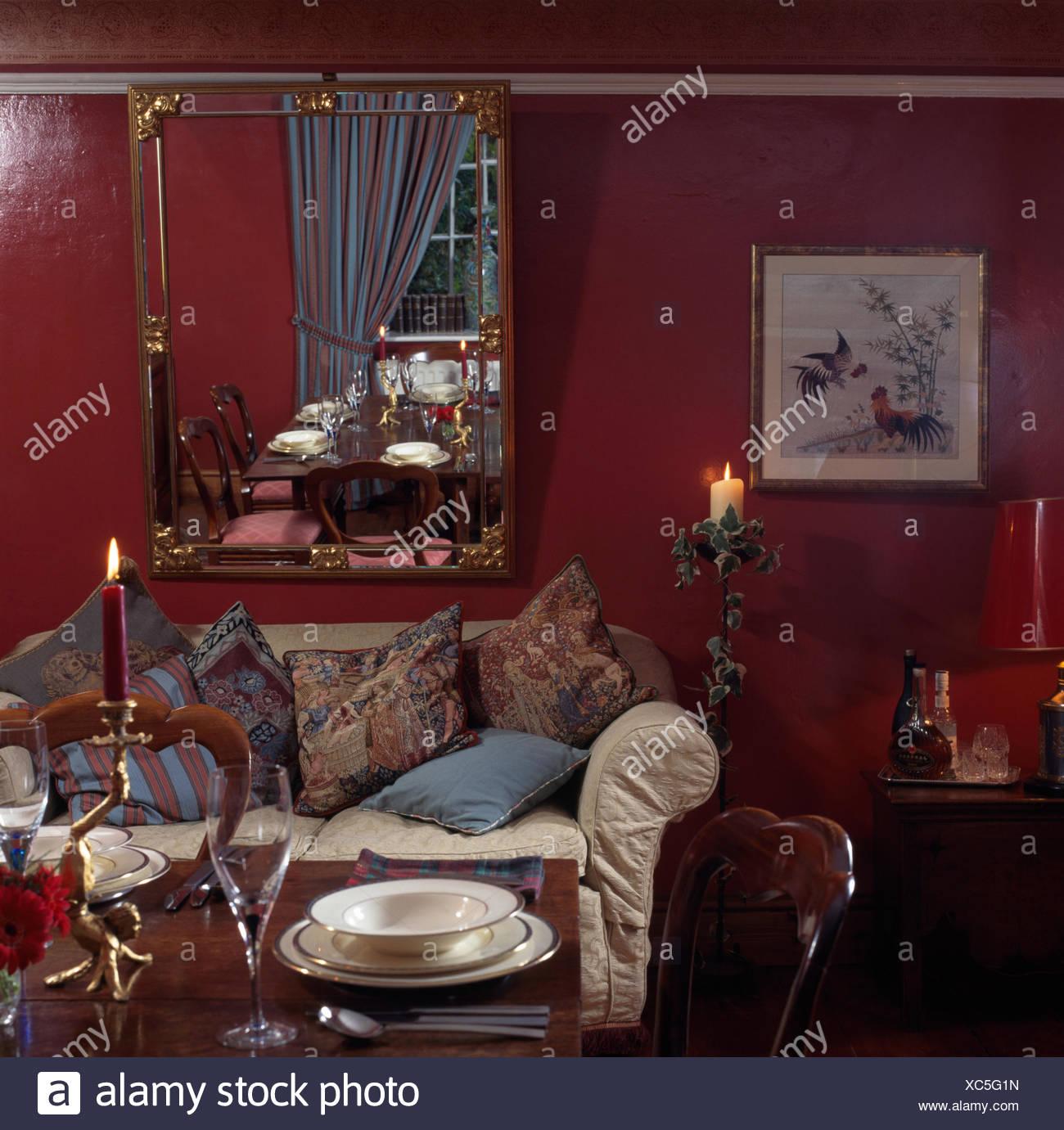 Vergoldeter Spiegel über Sofa Mit Kissen In Einem Dunklen Rot Esszimmer Mit  Tisch Für Das Abendessen Gestapelt