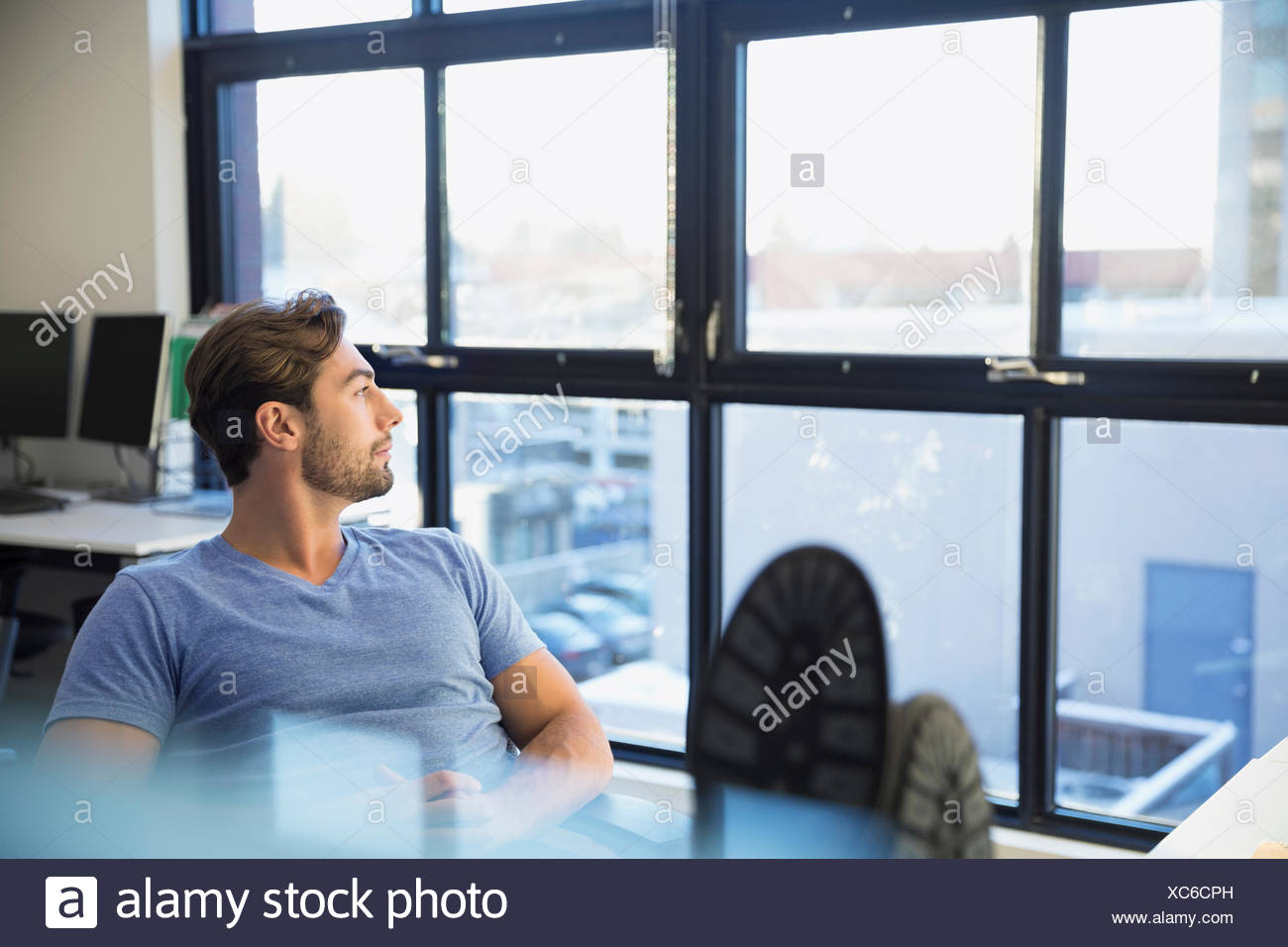 Nachdenklich Geschäftsmann mit Füßen, Blick aus Fenster Stockbild