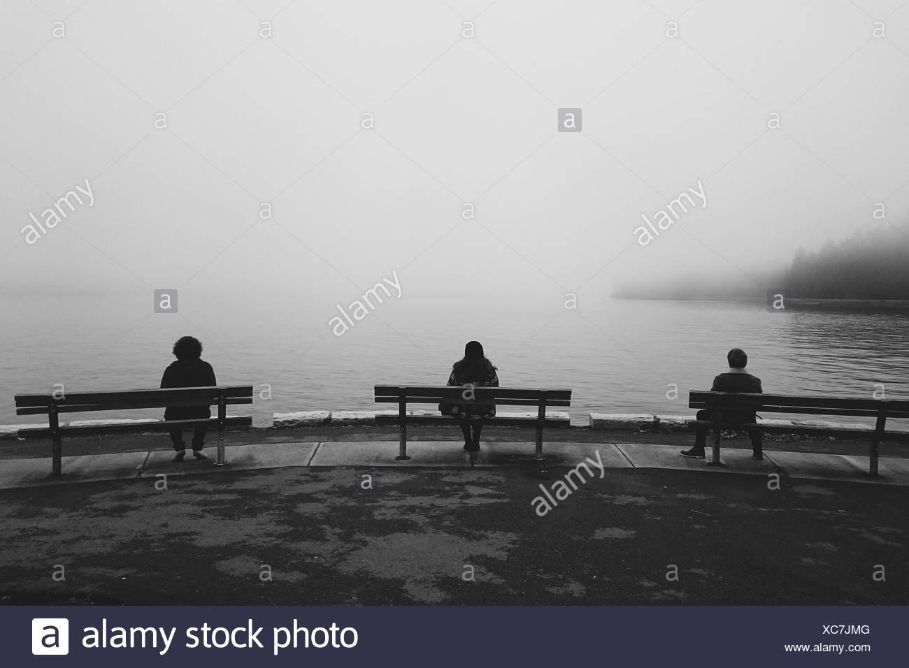 Drei Leute sitzen auf den Bänken am Seeufer Stockbild