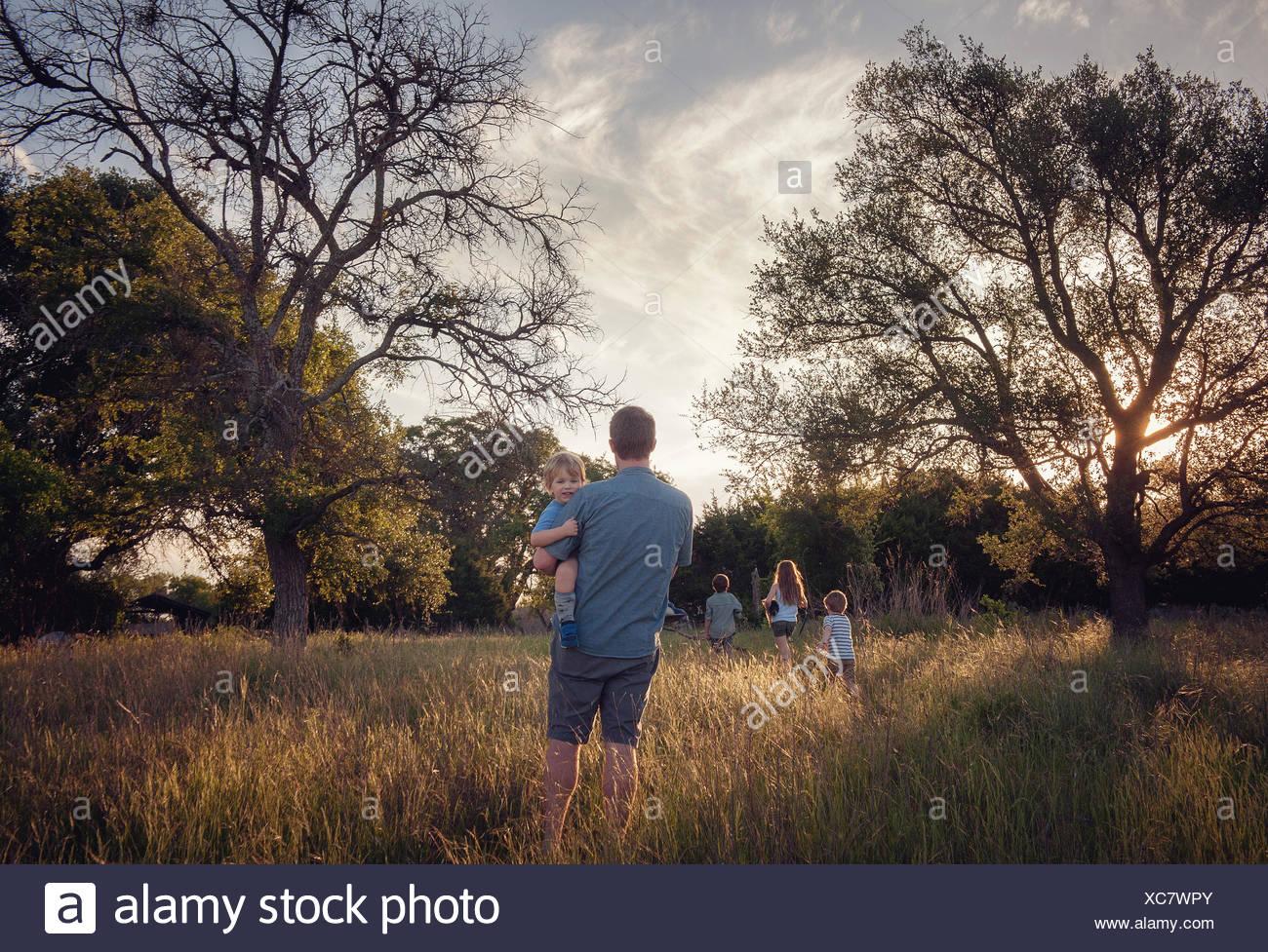 Vater und seinen vier Kindern zu Fuß in ländlichen Landschaft an der Dämmerung, Texas, Amerika, USA Stockbild