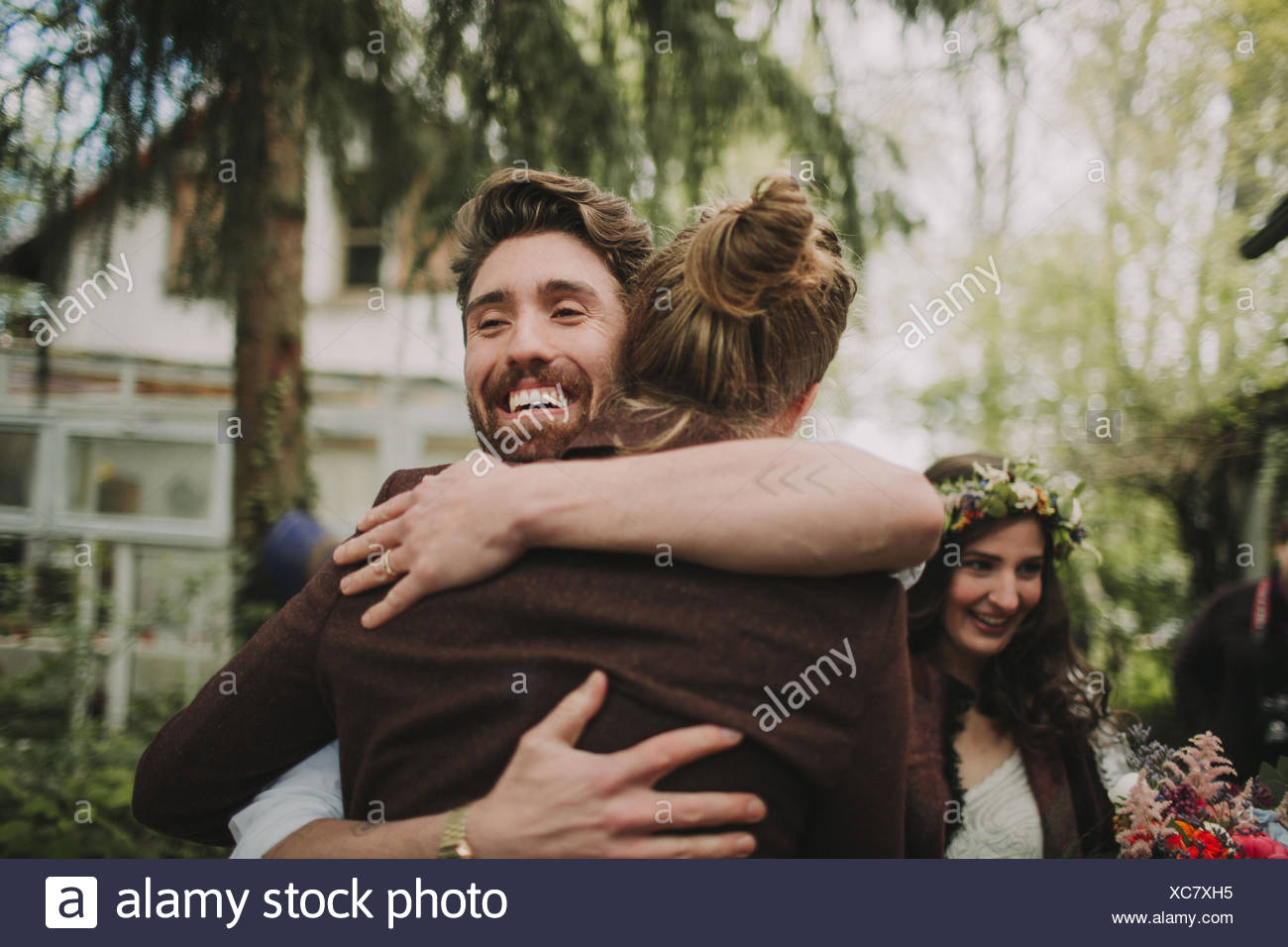 Alternative Hochzeit, Freund umarmt den Bräutigam Stockbild