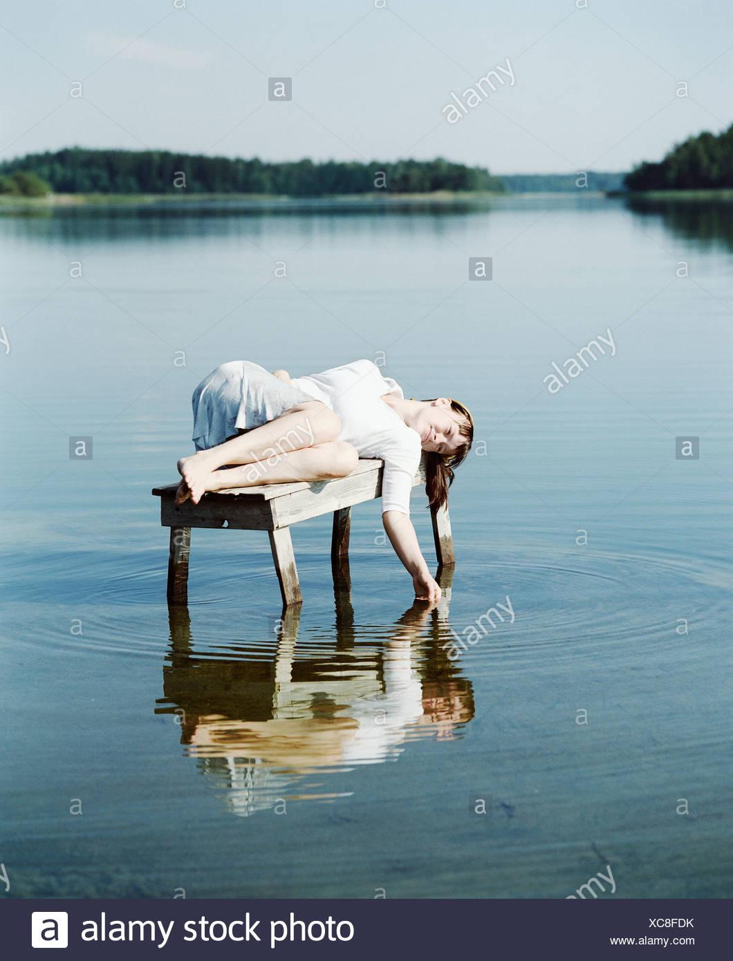 Junge Frau auf einer Bank in einem See Finnland liegend Stockbild