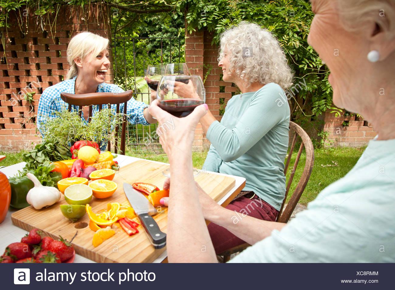 Drei Generationen Frauen mit einem Glas Rotwein während der Zubereitung von Speisen am Gartentisch Stockfoto