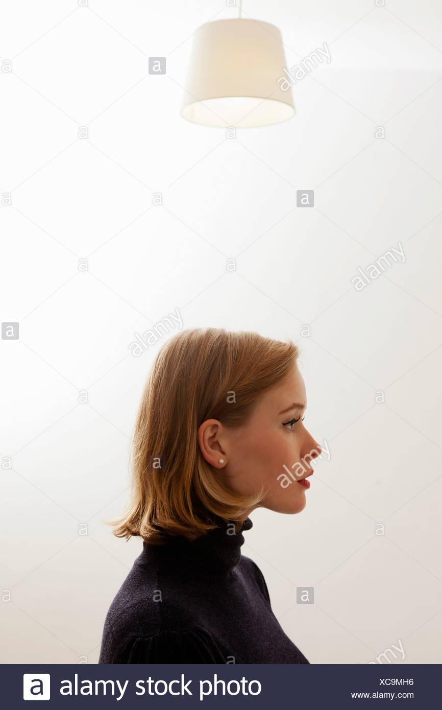 Frau stehend unter Deckenleuchte Stockbild