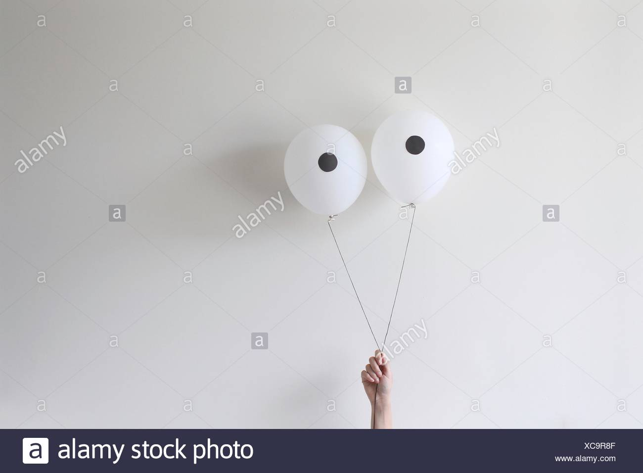 Eine Hand hält ein paar Ballons, die wie Augen Aussehen Stockfoto