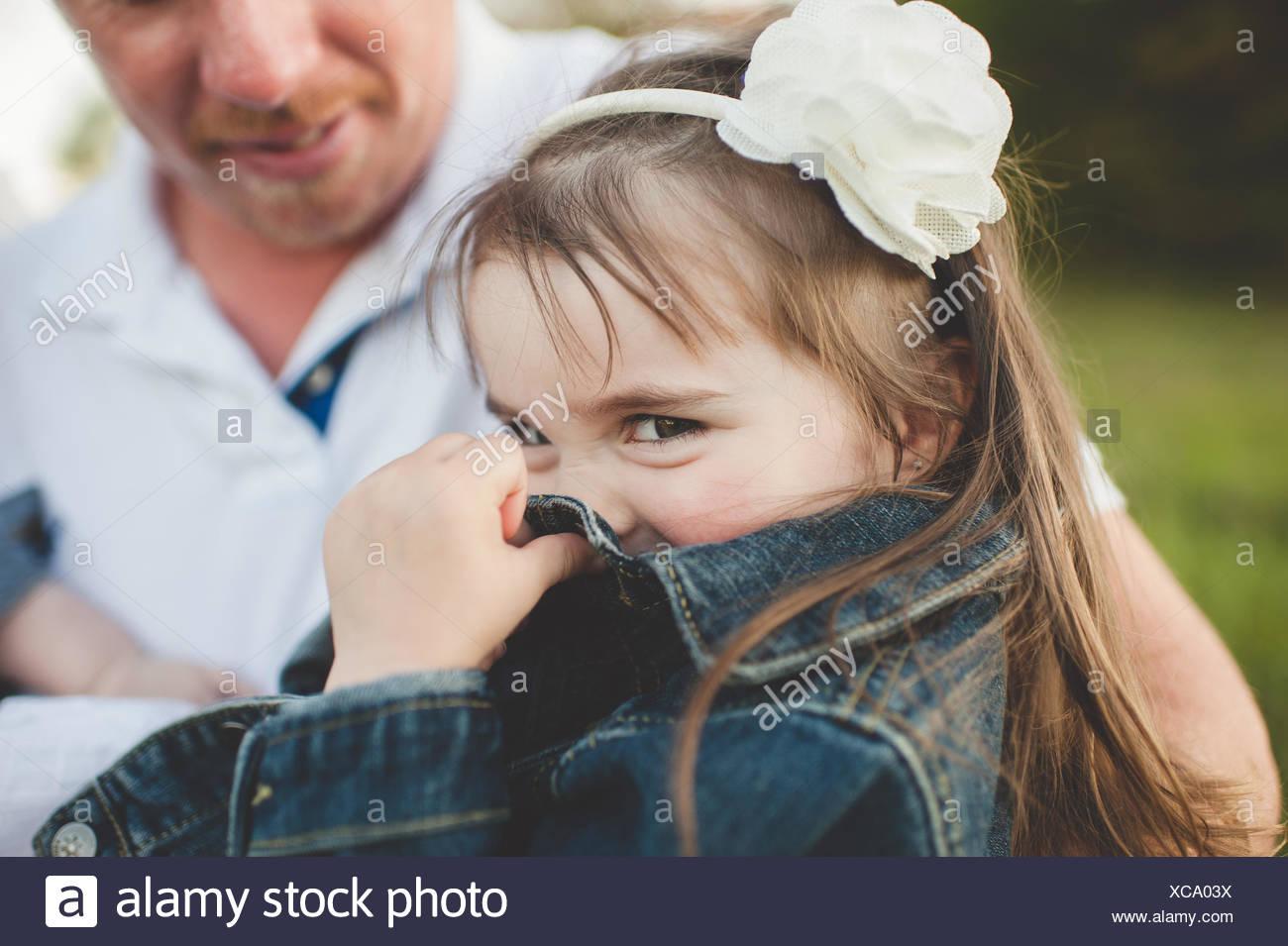 Junge Mädchen sitzt mit ihrem Vater, Gesicht mit Jacke versteckt Stockbild