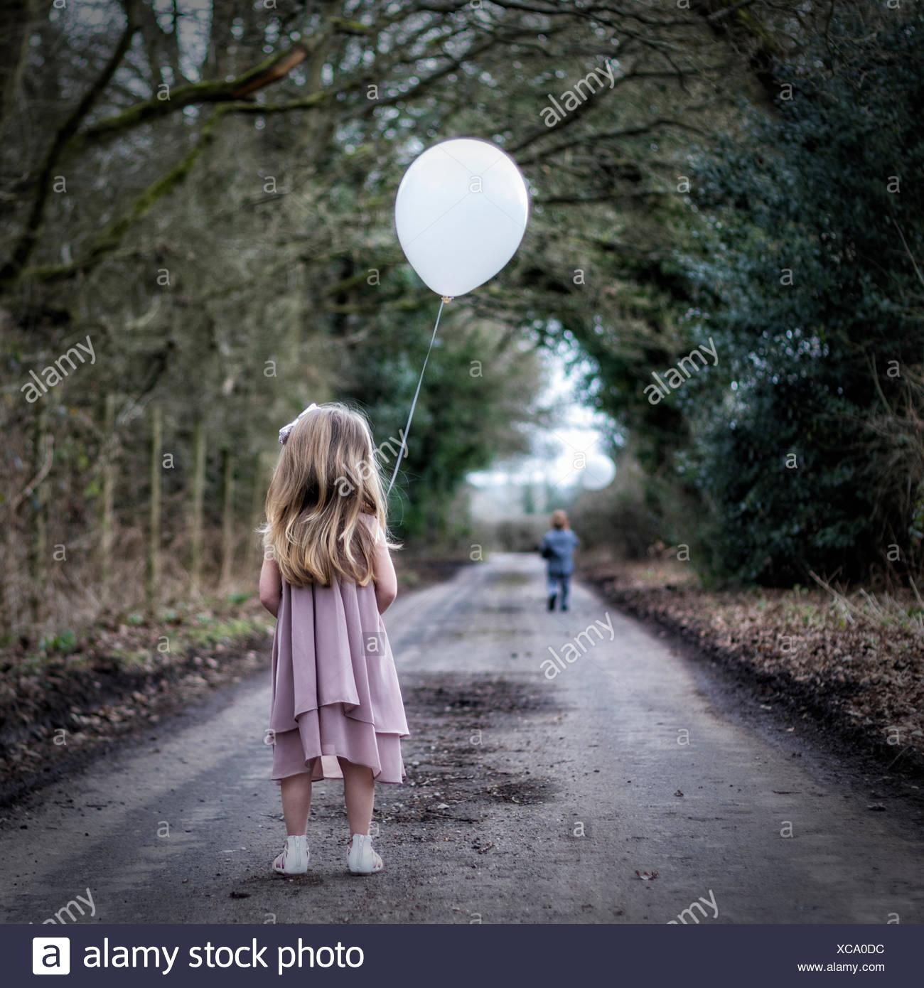 Rückansicht des Mädchens mit einem Ballon Blick auf junge auf der Flucht vor ihr Stockbild