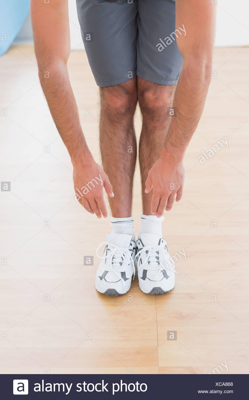 Mann berühren, Hände, Füße im Fitness-studio Stockbild