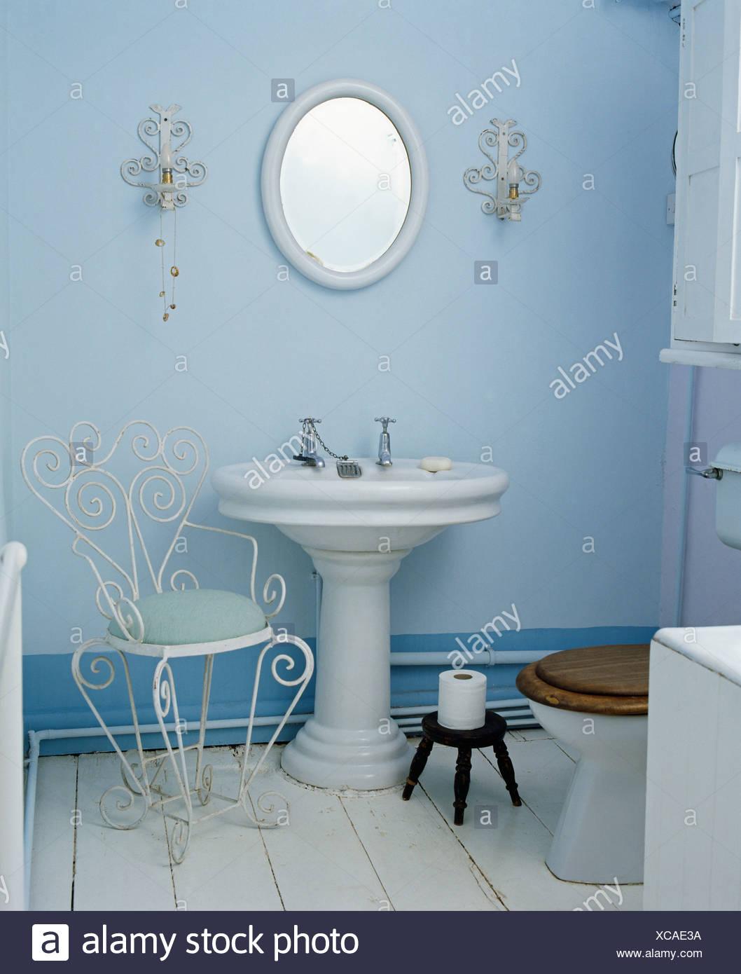 Weißen Sockel Becken und Metall Stuhl in blassen blauen Badezimmer ...