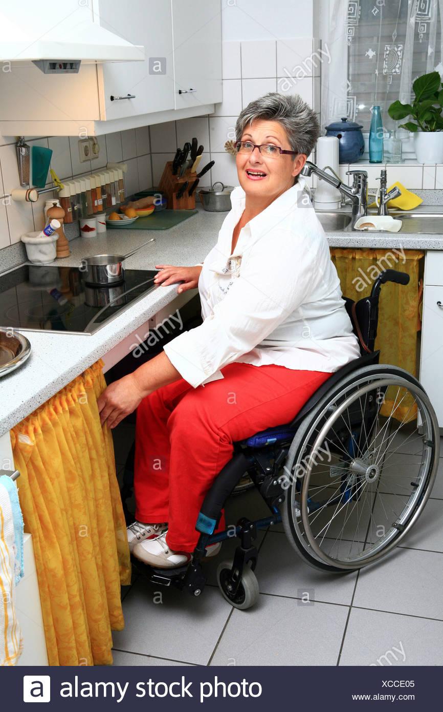 Frau in einem Rollstuhl in der Küche Stockfoto