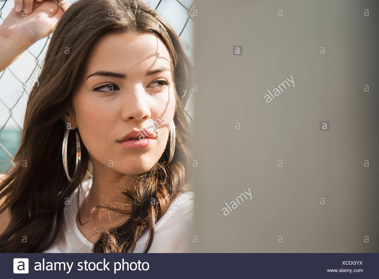 Junge Brünette Frau trägt Ohrringe Stockbild