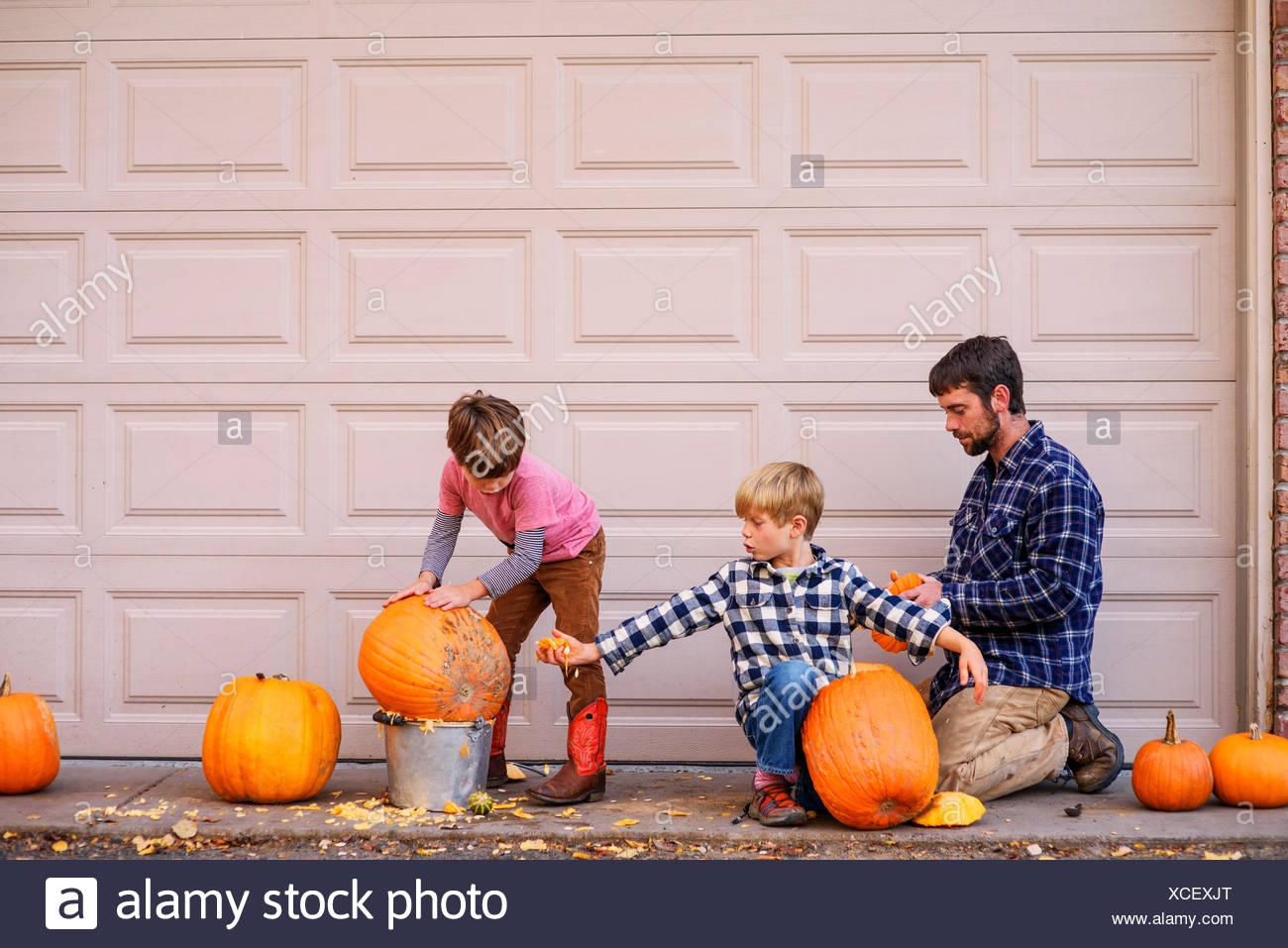 Zwei Jungs und ihr Vater schnitzen Halloween Kürbisse Stockfoto