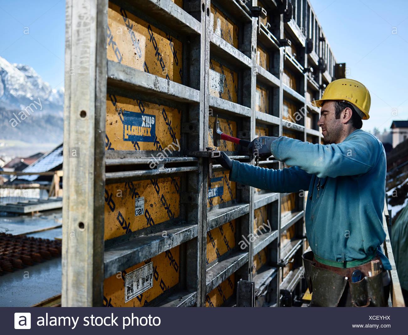 Bauarbeiter mit Hammer, verbindendes Element auf Schalung Wand, Innsbruck Land, Tirol, Österreich Stockbild