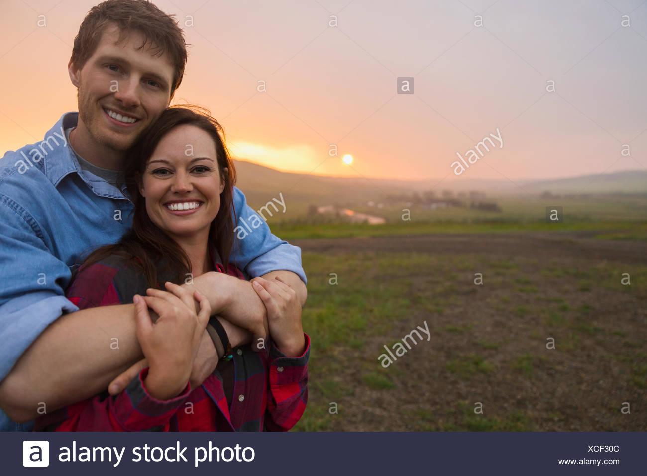 Porträt von paar umarmt im Feld bei Sonnenuntergang Stockbild