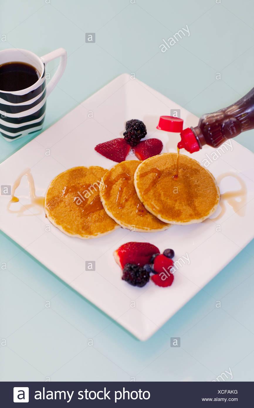 Sirup gegossen auf Pfannkuchen Stockbild