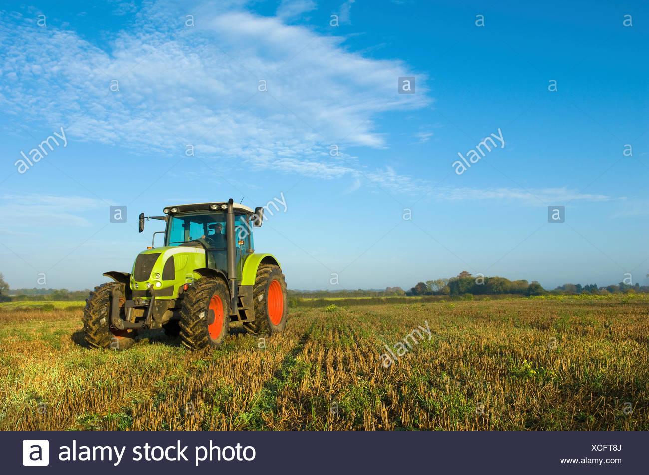 Ein Traktor in einem Stoppelfeld in Gloucestershire. Stockbild