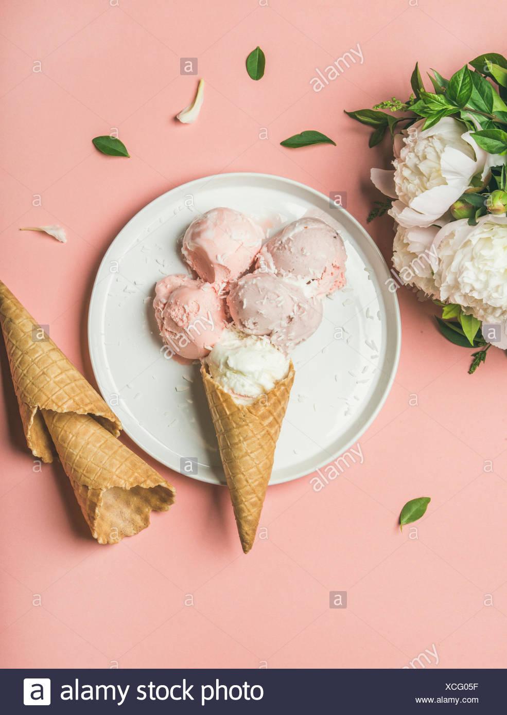 Flatlay Pastell rosa Erdbeer-Kokos-Eis schöpft, süße Zapfen auf weißem Teller und weißen Pfingstrosen über Pastell rosa Hintergrund, Draufsicht, ve Stockbild