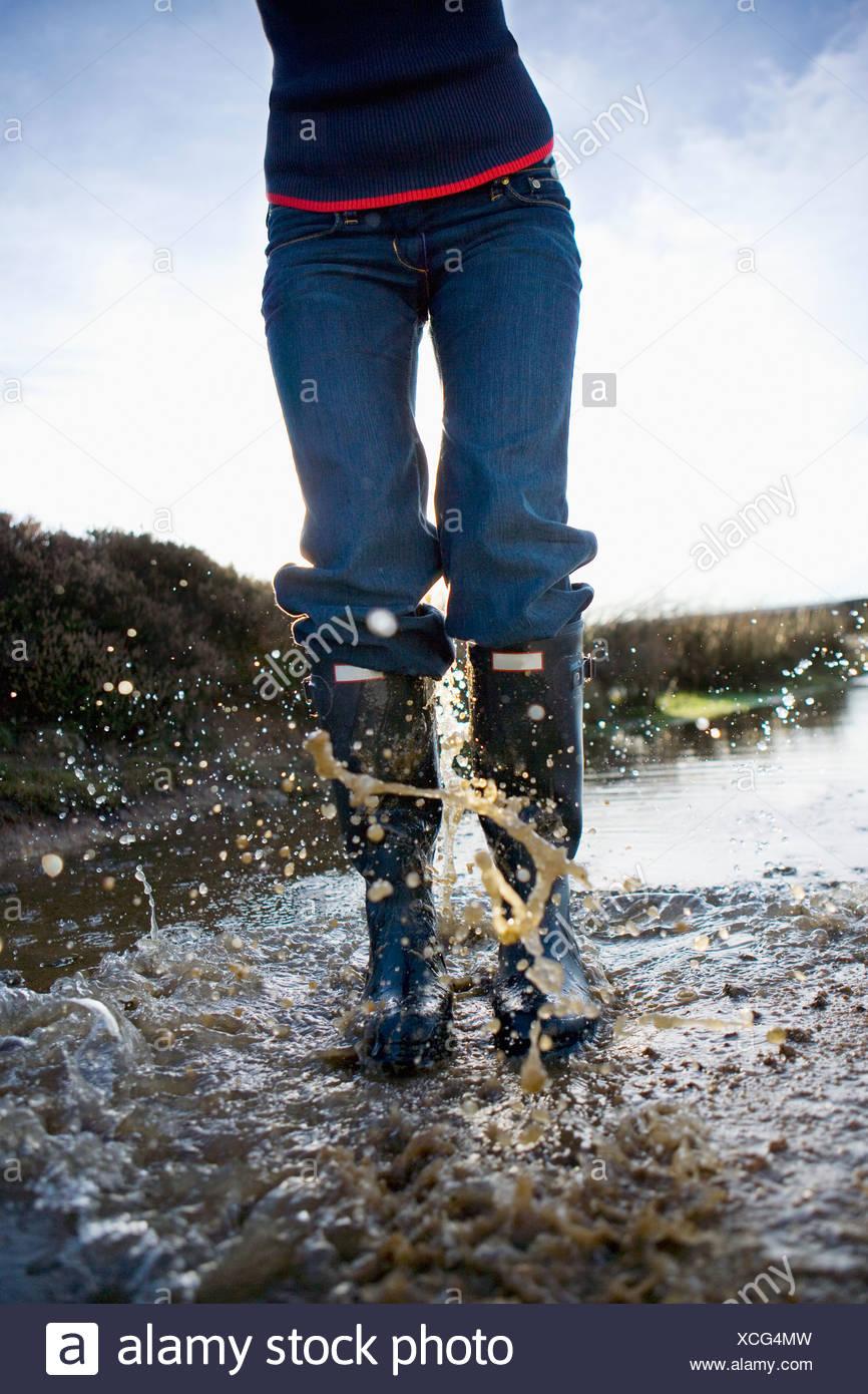 Frau in Gummistiefel im Wasser plantschen Stockbild